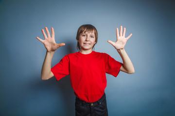 European-looking boy of ten years shows a figure ten fingers on