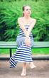 Young beautiful fashionable woman wearing striped dress sitting