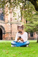 Young lady with mobile phone sitting in Glasgow University garde