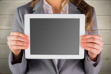 Composite image of businesswoman showing a tablet pc
