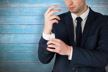Composite image of handsome businessman adjusting his cuffs