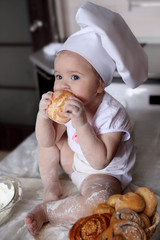 Child chef hat eats muffin