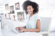 Composite image of happy businesswoman working on her laptop