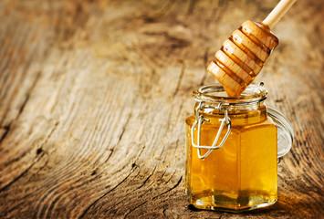 Honey dipper above a jar on an old vintage wood