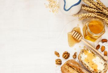 Rural or country breakfast - bread rolls, honey jar and milk
