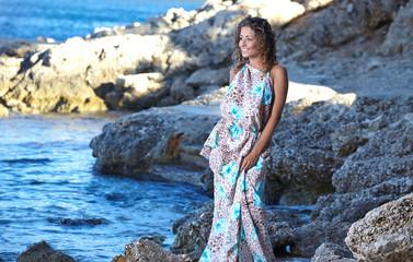 woman in a blue dress on the ocean coast