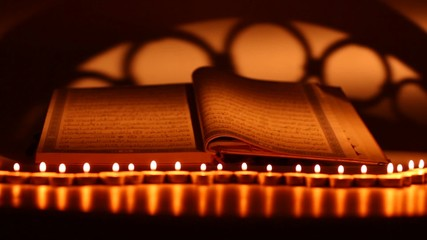 Quran the holy book of Islam with candles in front, dolly shot