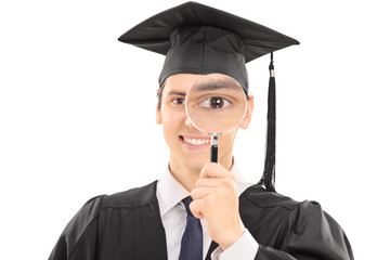 College graduate looking through magnifying glass