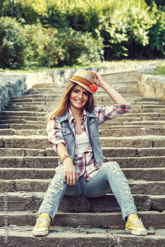 canvas print picture Cheerful young woman sitting on concrete stairs