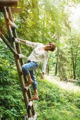 Young caucasian brunette posing on the wooden ladder