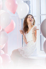 laughing girl sits on a windowsill with balloons in hand