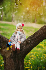 Little adorable girl sitting on blossoming tree in apple garden