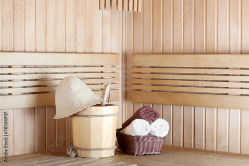 Traditional wooden sauna for relaxation with bucket of water and - 78366907
