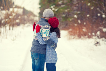 Young couple wearing a sweaters hugging outdoors in winter
