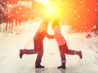 Young happy couple in love kissing outdoors inwinter at sunset