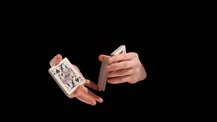 Unusual trick with cards on black background, slow motion