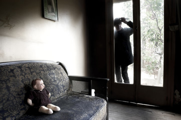 Killer looking through dirty glass of the back door