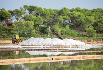 Salt evaporation pond with tractor and conveyor.