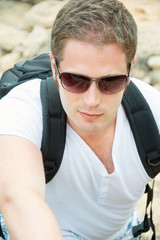 Portrait of male tourist with backpack climbing mountains.