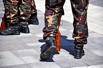 Military soldiers' legs in camouflage uniform