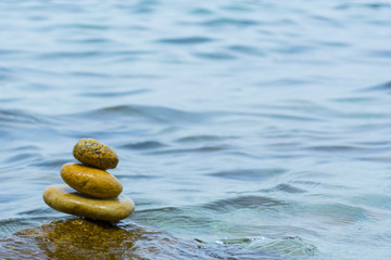 Stack of stones with sea water background