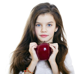Portrait of a beautiful little girl holding a red apple