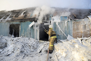 Firefighter extinguishes a fire in a wooden house in the winter.