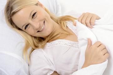 Frau beim Ausschlafen im Bett