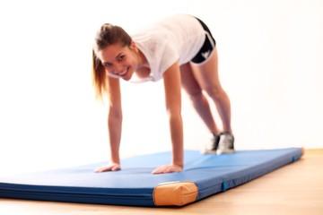 Junge Frau macht Übungen auf Turnmatte
