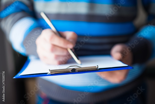 businessman holding a clipboard and write on it - 78381716