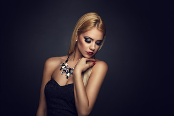 Beautiful blonde with nice makeup posing on a dark background