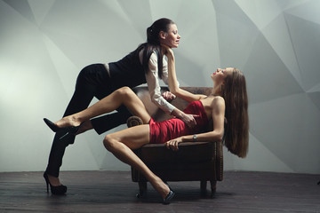 Beautiful lesbian flirting couple in the chair.