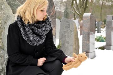 Mutter legt Teddy auf Grab von Kind