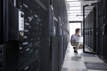 Technician, kneeling with laptop, checking aisle of server storage cabinets