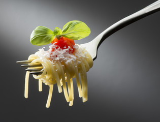 fork with spaghetti tomato sauce and basil on dark background