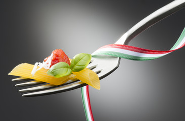 fork with macaroni tomato sauce and basil on dark background