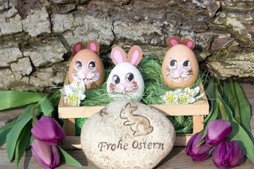 Lustige Ostereier mit Gesicht und lila Tulpen