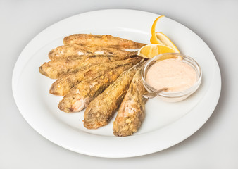 Fried little sea fish with sauce and lemon