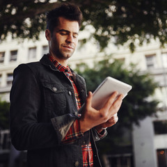 man using tablet in urban setting