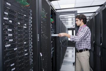 Technician replacing server in server cabinet
