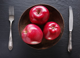Red apples and table settings on a grey background.