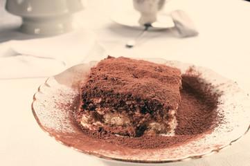 Slice of homemade tiramisu dessert in instagram warm tone