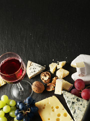 Different types of cheeses with wine glass and fruits.
