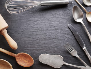 Cooking utensils on a dark grey background.