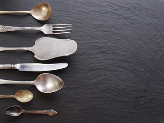 Cooking utensils on a dark grey background.