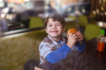 Little boy smile with hamburger in fast food restaurant