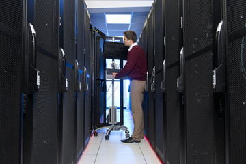 Technician, on computer, working on server rack in data center