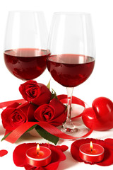 Composition with red wine in glasses, red roses, ribbon and