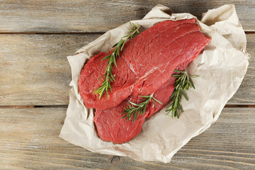 Raw beef steak with rosemary on paper on wooden background