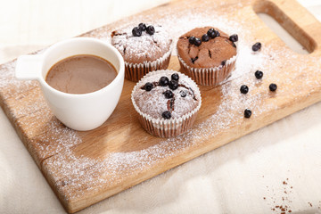 Delicious chocolate muffins on wooden board